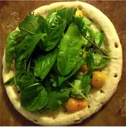 Uncooked pizza topped with greens